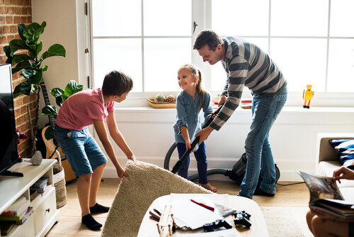 family in living room moving rug